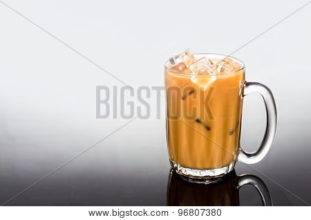 Refreshing ice cold coffee with milk in transparent glass flushed right in dual tone background