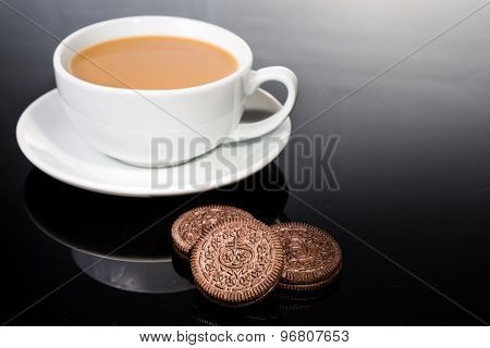 Creme-filled sandwich cookies and coffee cup on dark reflective background