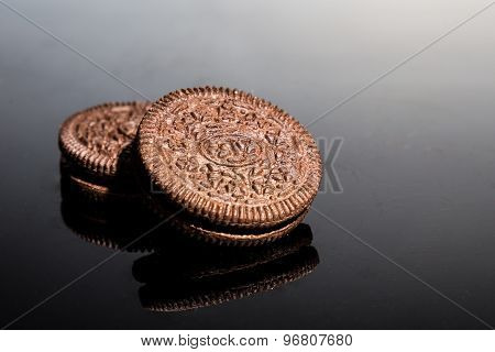 Creme-filled sandwich cookie on dark reflective background