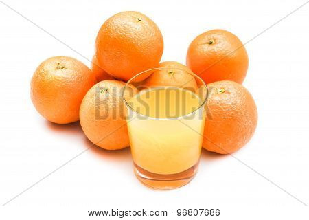 Fizzy orange juice from effervescent tablet with oranges at backdrop