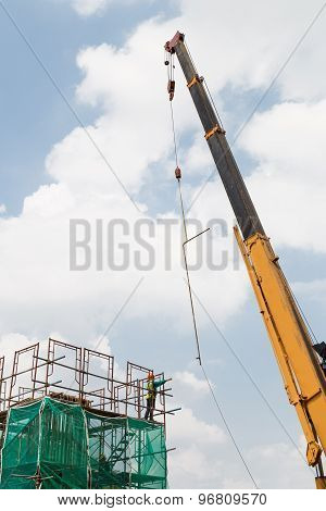 A worker receiving a steel rod from a crane in the construction of a big column.