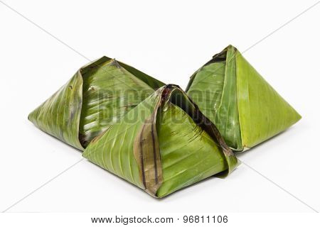 Three packs of simple and authentic nasi lemak wrapped in banana leaf, popular food in Malaysia