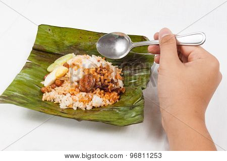 Savoring the simple and authentic nasi lemak wrapped in banana leaf.