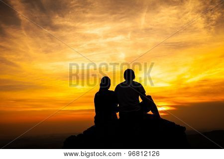 Silhouette of loving couple sitting on a rock in sunset