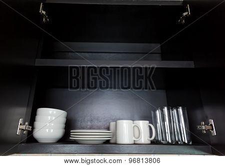 White Kitchenware In Black Cupboard