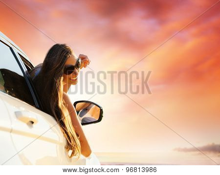Woman driver smiling in evening sunset. Concept of traveling. Beautiful caucasian young woman.