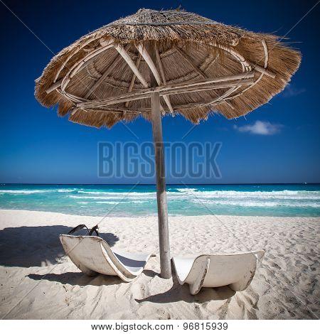 Caribbean Sea Coastline With Grass Sun Umbrella And Wooden Beach Beds