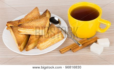 Sweet Puff Pastries In Glass Plate And Tea In Cup
