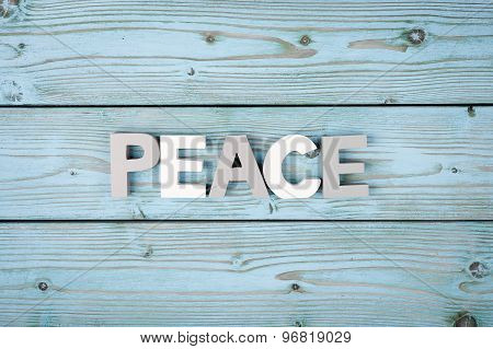 Signs PEACE on the wooden background.