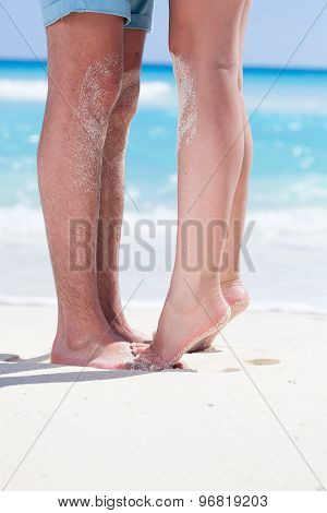 Couple Of Male And Female Legs On Beach