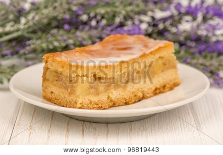 A piece of apple pie on the wooden background.