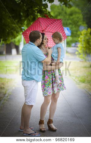 Young Happy Family Under Umbrella