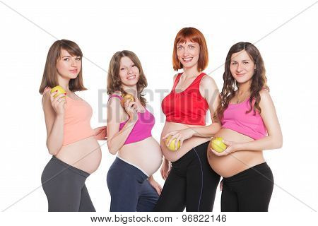 Portrait of four happy pregnant women with fruits are looking at the camera. Healthy maternity conce