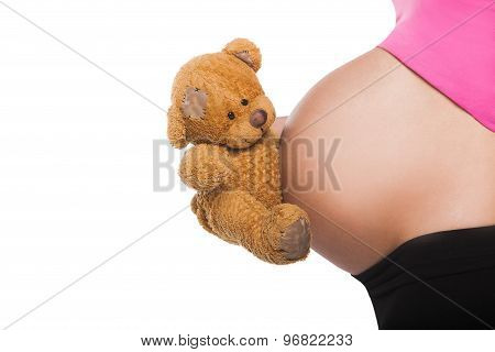 Close up of pregnant belly with toy. Woman expecting a baby holding cute teddy bear.