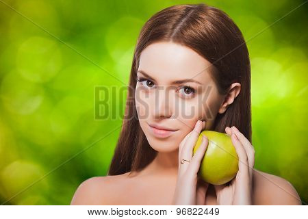Portrait of brunette woman holding an apple on green eco background.