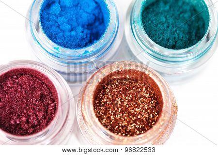 Set of glass jars with metallic glossy eye shadows on white background