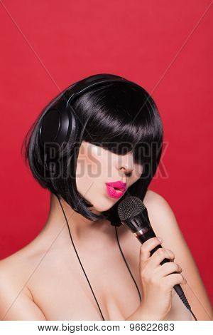 Stylish girl singing with a mike, red background. Karaoke
