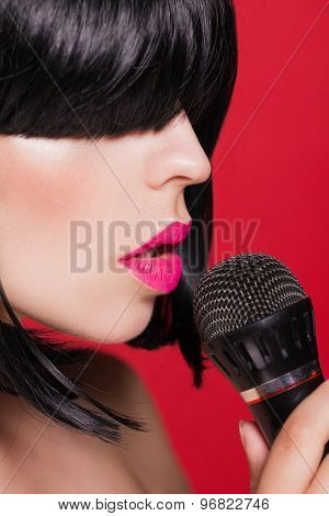 Stylish woman with a microphone, red background. Karaoke