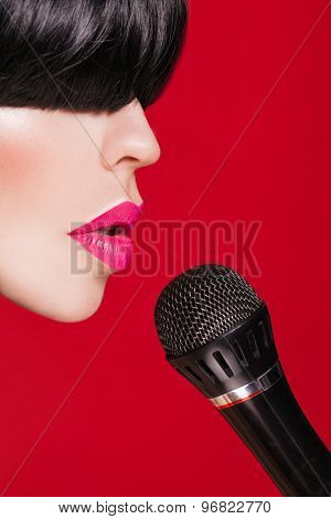 Stylish woman model with a microphone, red background. Karaoke
