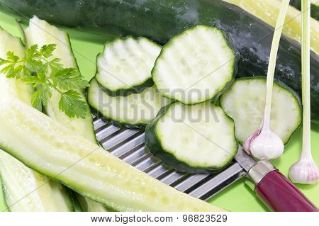 Sliced Cucamber And Marrow Squash  Ordered On Top Of The Chopper On Green Background