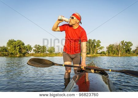 senior kayak paddler drinking water or sport drink after paddling workout on a lake in summer