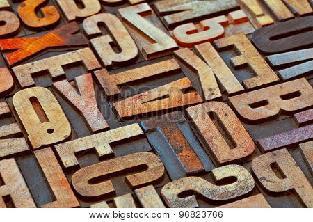 alphabet abstract in vintage letterpress wood type printing blocks stained by color inks