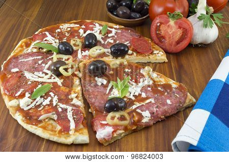 Sliced Round Pizza And Raw Vegetables On A Wooden Table