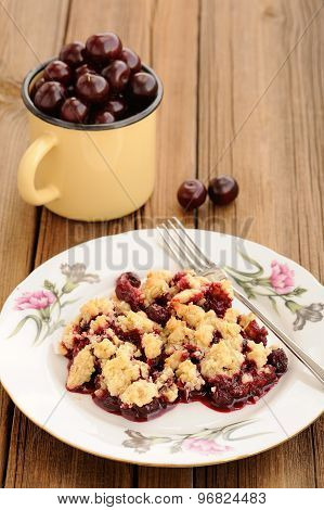 Piece Of Homemade Cherry Crumble With Fork And Yellow Metal Cup With Cherries On The Background