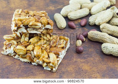 Honey Bar With Peanuts Almonds And Hazelnuts Surrounded By Roasted And Raw Peanuts Placed On A Woode