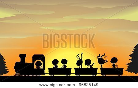 Silhouette of monkeys sitting on a train with sunset in the background