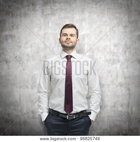 Confident Businessman With Hands In Pockets. Concrete Background.