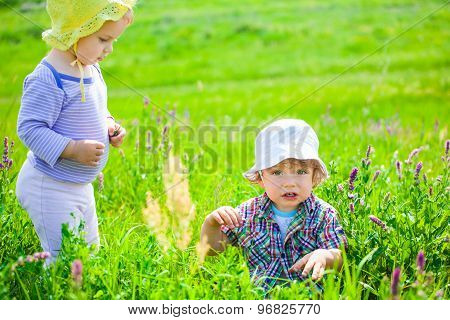 Baby Boy And Baby Girl On A Meadow