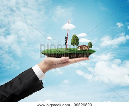 Hand Holding Landscape With Eco Wind Turbine