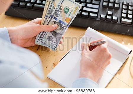 Accountant Holding Cash And Taking Notes