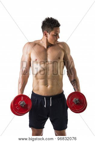 Muscular shirtless young man exercising traps with dumbbells