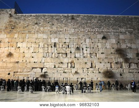 Orthodox Jewish men praying at the Western Wall in Jerusalem before evening