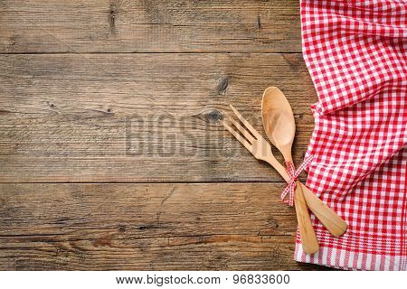 Kitchenware on wooden table with a red checkered tablecloth