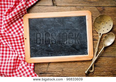 Kitchenware on a blackboard with a red checkered tablecloth