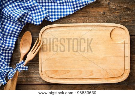 Wooden spoon on a cutting board with a blue checkered tablecloth
