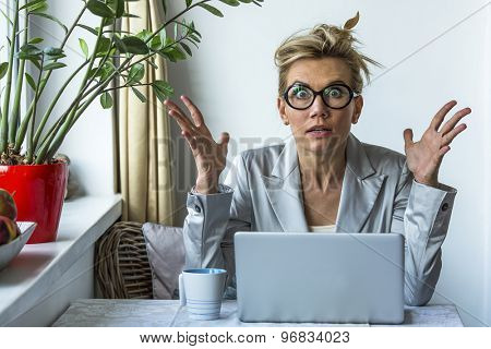 Shocked business woman with laptop in office.