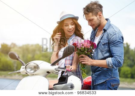 A man gives flowers beautiful woman. In the background the river and scooter