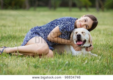 A Girl Plays With A Dog On The Grass. Training The Dog