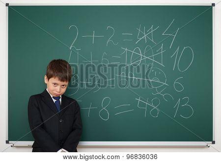Schoolboy near the school board solve math