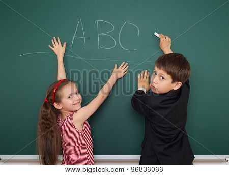 boy and girl write abc on school board