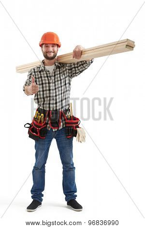 smiley builder in uniform showing thumbs up and holding long wooden boards. isolated on white background