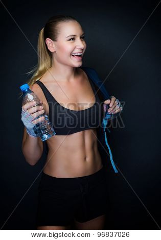 Happy healthy sportive woman over dark background, fitness trainer wearing sport outfit and holding bottle of water, healthy lifestyle