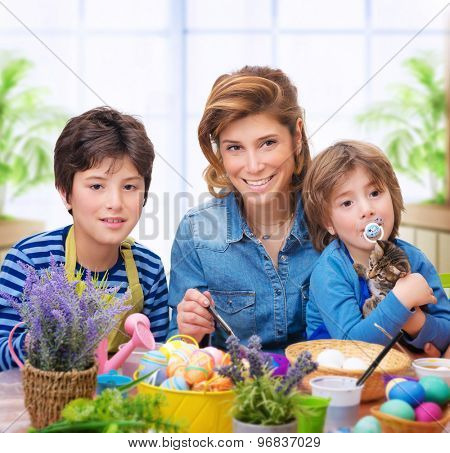 Happy family coloring eggs, mother with two little sons paint traditional Easter eggs in different colors at home, enjoying family tradition