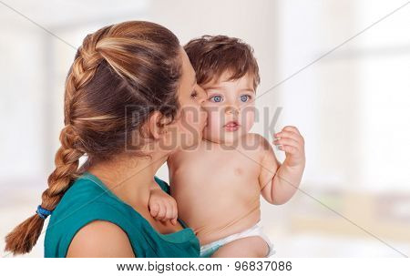 Portrait of happy young mother holding on hands cute little son and kissing him with love, with pleasure spending time at home, enjoying motherhood