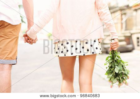 A midsection of a romantic couple walking in the city
