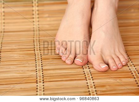 Care for beautiful woman legs on the bamboo floor